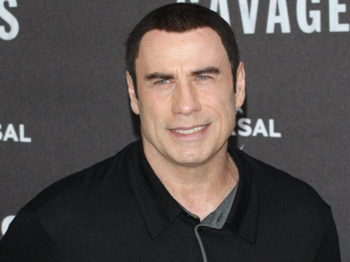 John Travolta wears a casual black jacket on the red carpet
