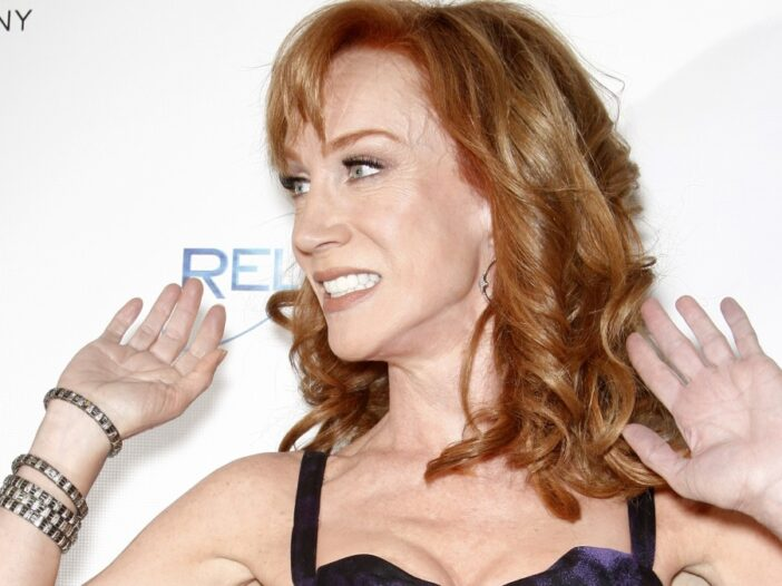 Kathy Griffin, wearing a black dress, holds her hands up against a white background on the red carpet