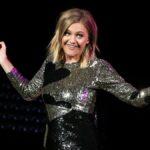 Kelsea Ballerini, wearing a silver dress festooned with black hearts, shrugs onstage