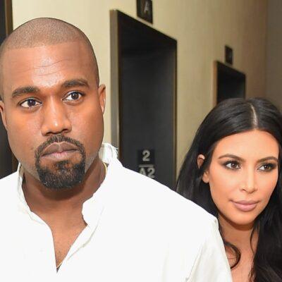 Kanye West, wearing a white shirt, and Kim Kardashian, in brown, walk through a hallway