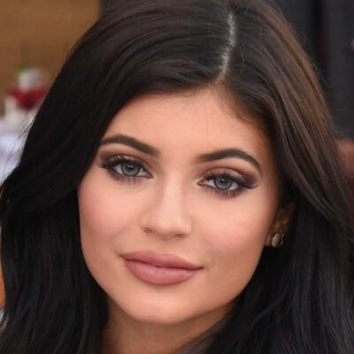 Kylie Jenner smiles demurely for the camera while attending a luncheon
