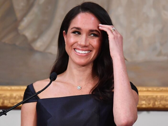 Meghan Markle smiles as she wears a black dress and pushes her hair back while giving a speech