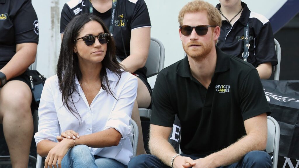 Meghan Markle, in a white top, sunglasses, and jeans, sits with Prince Harry, in a black top, sunglasses and jeans, at the Invictus Games