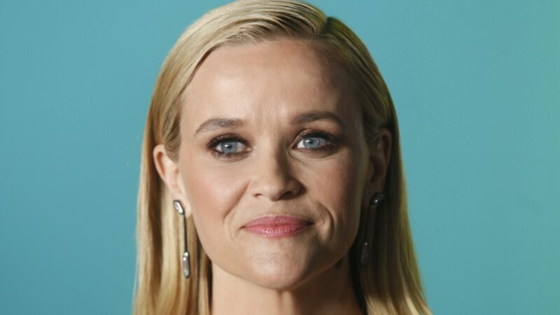 Reese Witherspoon stands before a teal background with her hair slicked behind her ears