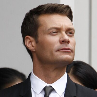 Ryan Seacrest wears a black suit and gazes out with a serious expression