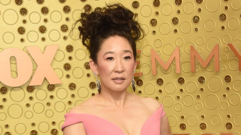 Sandra Oh wears a pink dress against a gold background on the red carpet
