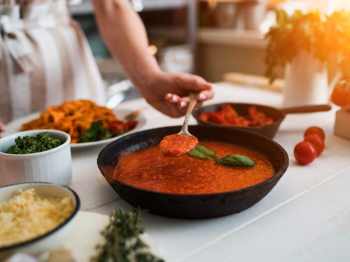 Image of woman making pasta sauce.