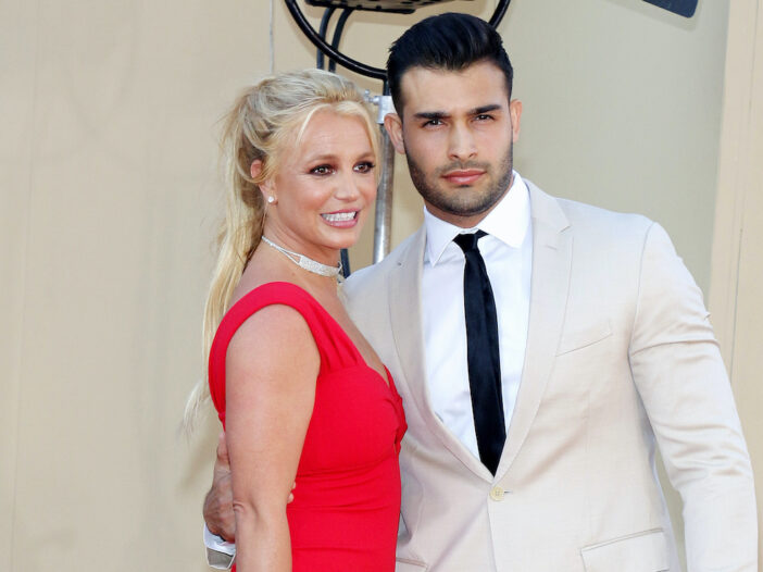 Britney Spears in a red dress with Sam Asghari in a tan suit
