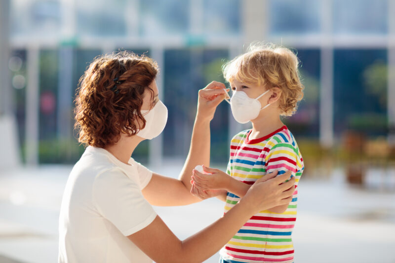 Image of mom helping son with mask