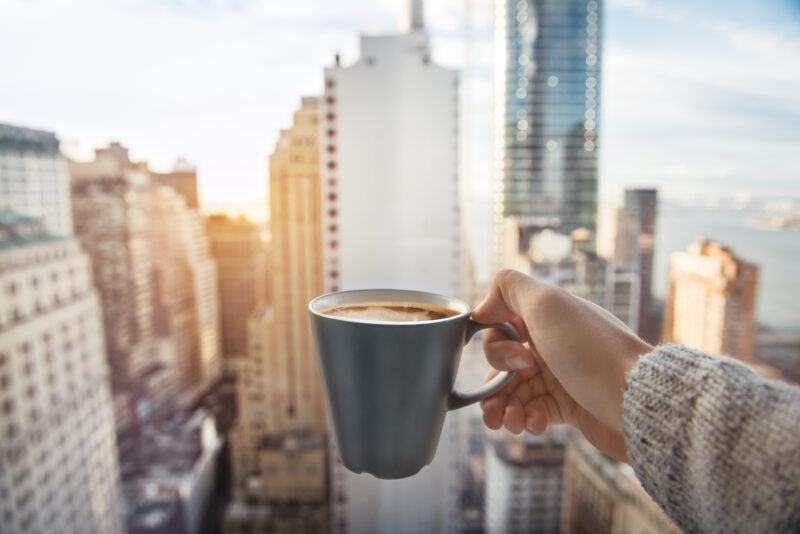 Image of person holding a mug in front of city.