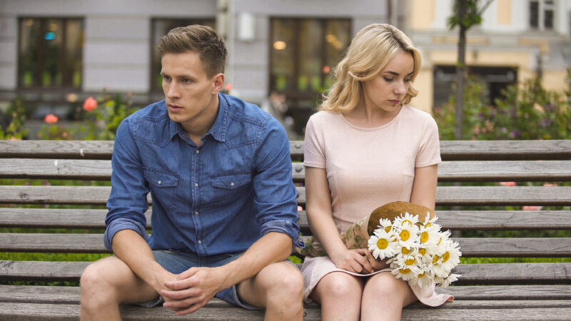 Unhappy couple sitting on bench.