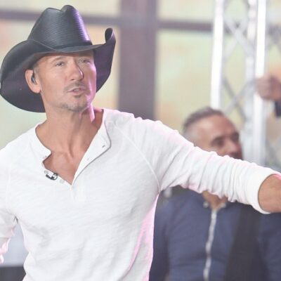 Tim McGraw wears a white shirt on stage as he performs in a black cowboy hat