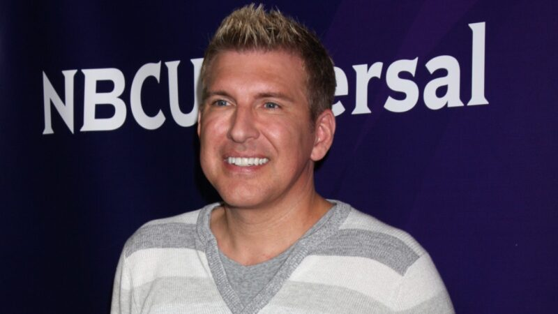 Todd Chrisley wears a gray striped shirt against a blue background on the red carpet