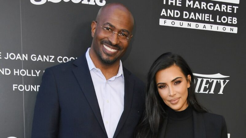 Van Jones, in a black suit, poses with Kim Kardashian, also in black, against a black background