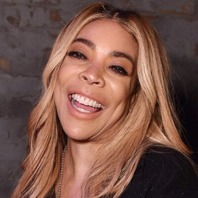Wendy Williams laughs at the camera while wearing a black top and jean shorts
