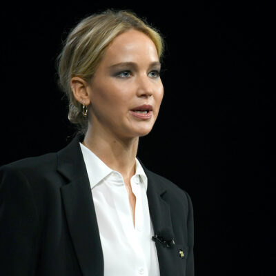 Jennifer Lawrence speaking in a black jacket and white shirt