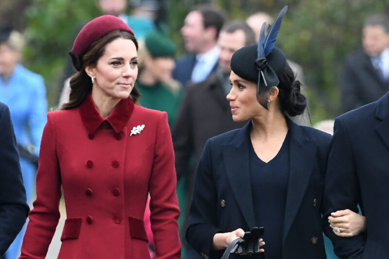 Meghan Markle in a black coat looking at Kate Middleton in a red coat outside