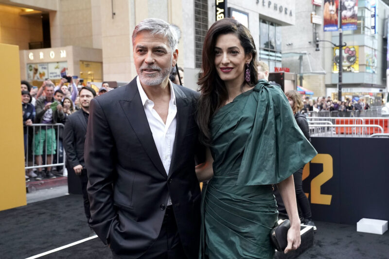 George Clooney in a black suit with Amal Clooney in a green dress outdoors