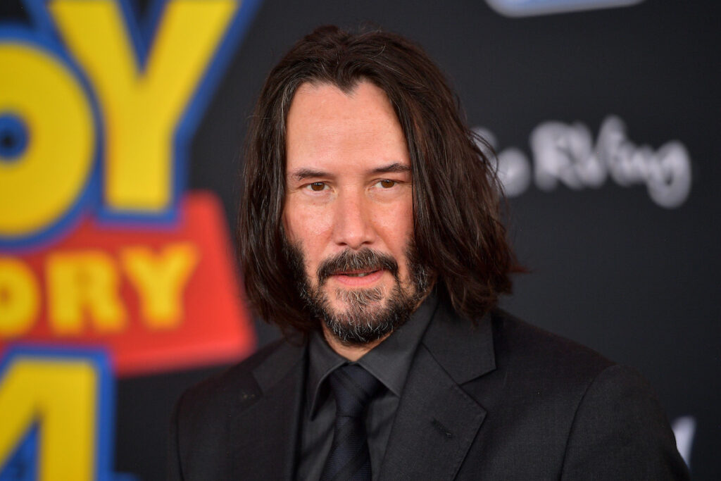 close up of Keanu Reeves in a black suit