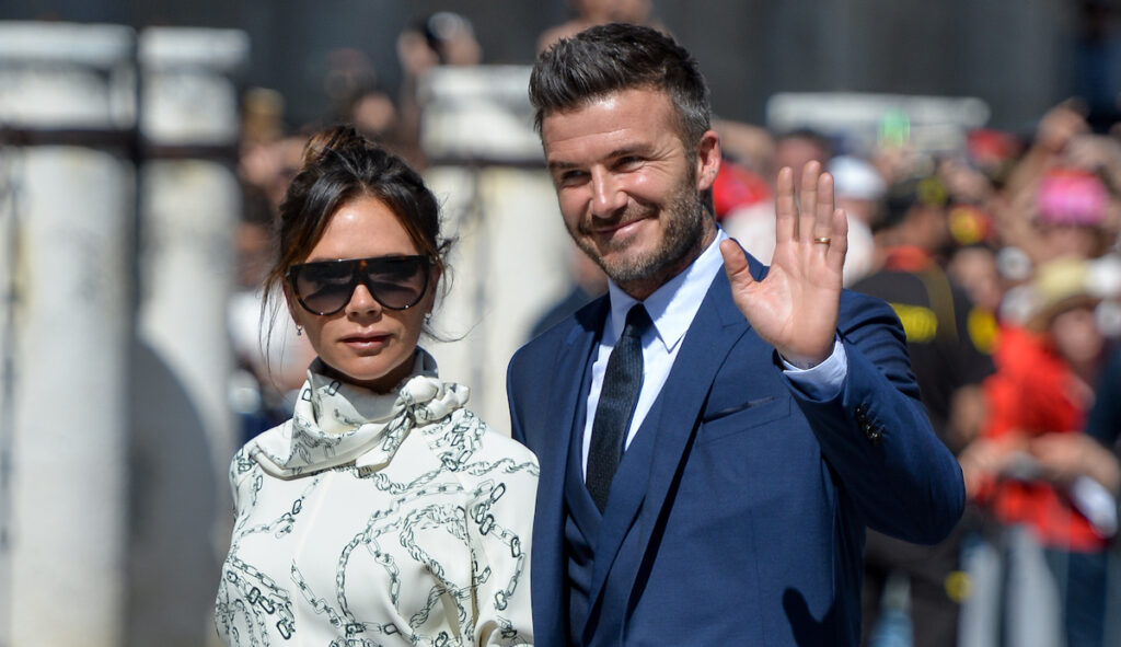 David Beckham waving in a blue suit, Victoria Beckham in sunglasses and a white dress