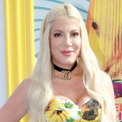 Tori Spelling smiling in a yellow dress