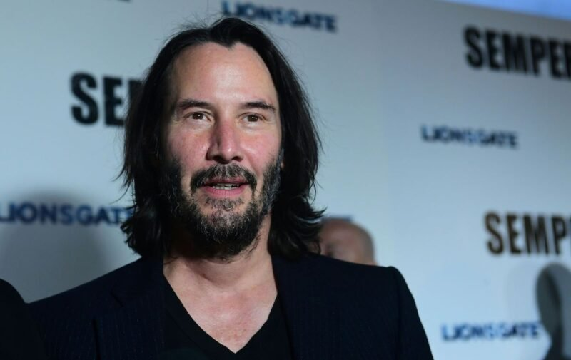 Keanu Reeves in a black shirt and jacket