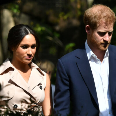 Prince Harry in a blue suit walking with Meghan Markle in a tan coat outdoors