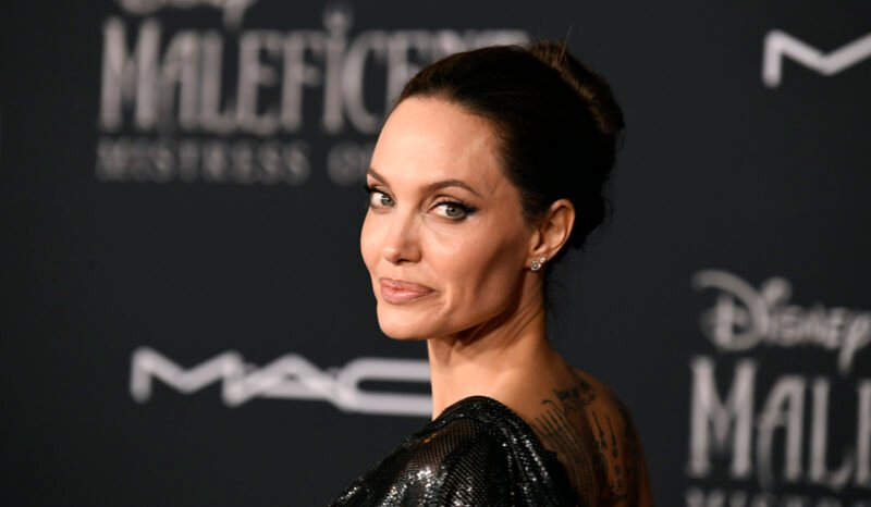 Angelina Jolie looking backwards in a black dress