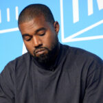 Kanye West looking down in a black t shirt