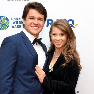 Chandler Powell smiling in a blue suit with Bindi Irwin in a black outfit