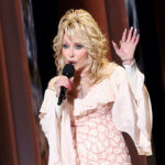 Dolly Parton singing on stage in a pink and white dress