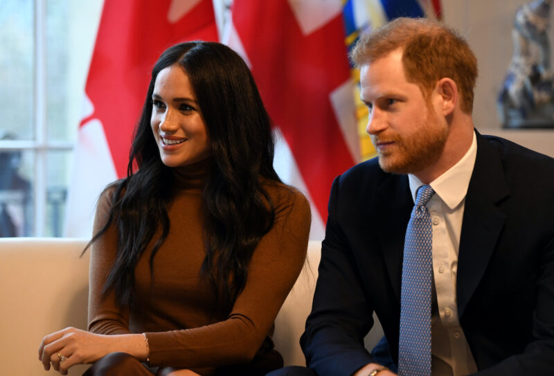 Meghan Markle in a brown sweater sitting with Prince Harry in a blue suit