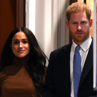 Meghan Markle in a brown sweater with Prince Harry in a blue suit