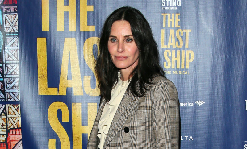 Courteney Cox in a tan jacket and yellow shirt