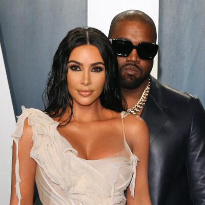 Kim Kardashian in a white dress with Kanye West in a leather jacket behind her