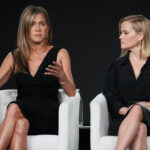 Jennifer Aniston and Reese Witherspoon in a black dresses sitting in white chairs on stage