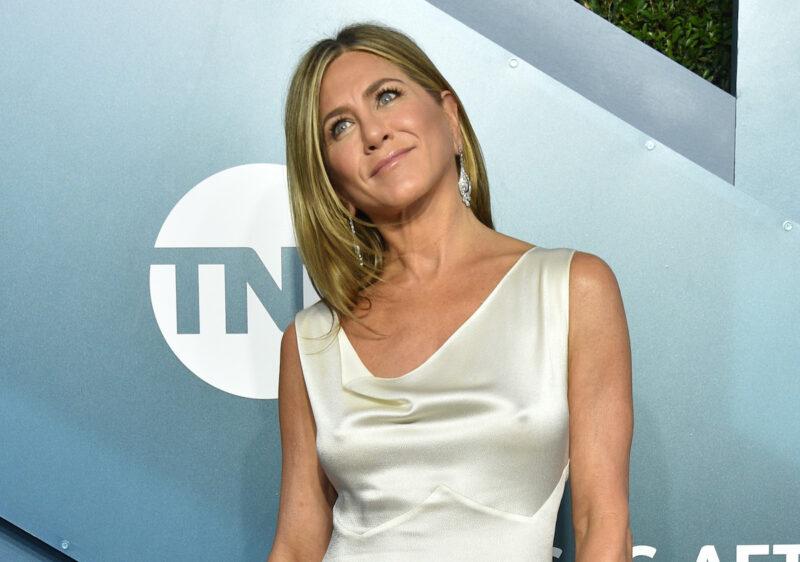 Jennifer Aniston smiling in a white dress
