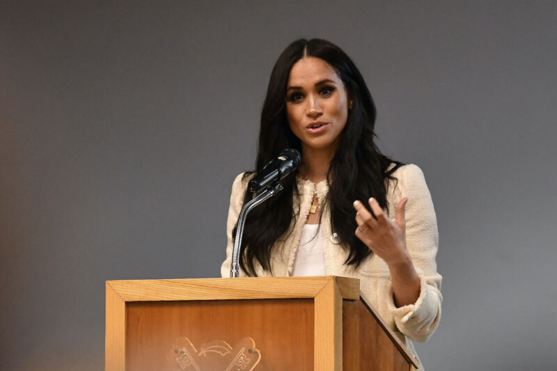Meghan Markle speaking at a podium in white