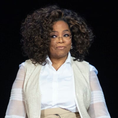 Oprah Winfrey smiling in a white and tan outfit