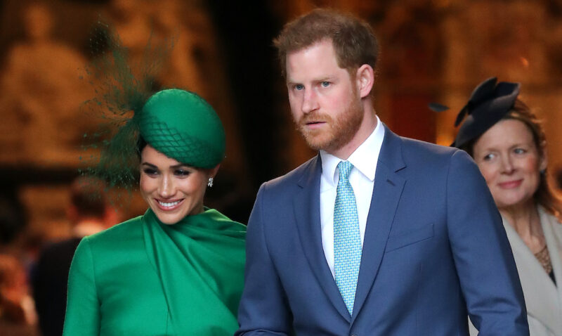 Meghan Markle in a green dress with Prince Harry in a blue suit