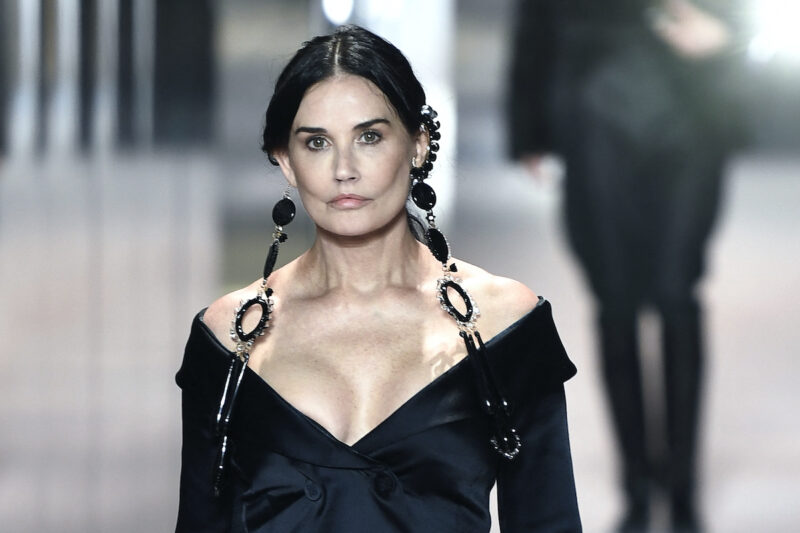 Demi Moore in a black dress on the runway