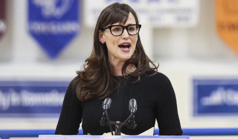 Jennifer Garner in a black sweater speaking at a podium