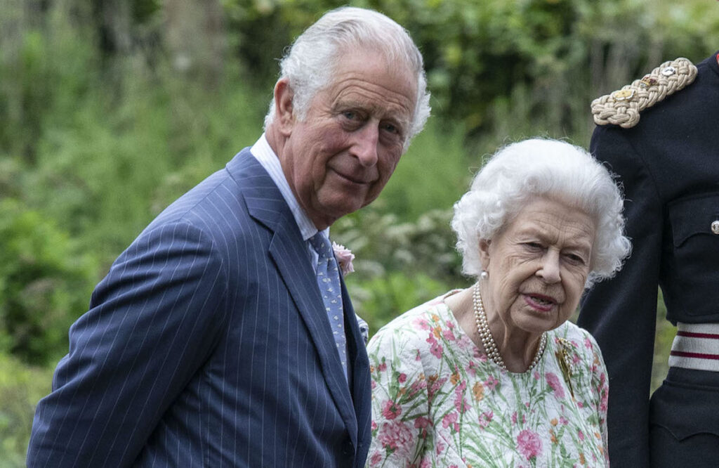 Prince Charles in a blue suit with Queen Elizabeth outdoors