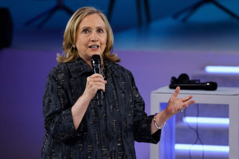 Hillary Clinton in a dark outfit speaking on stage
