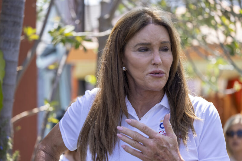Caitlyn Jenner talking outdoors in a white polo