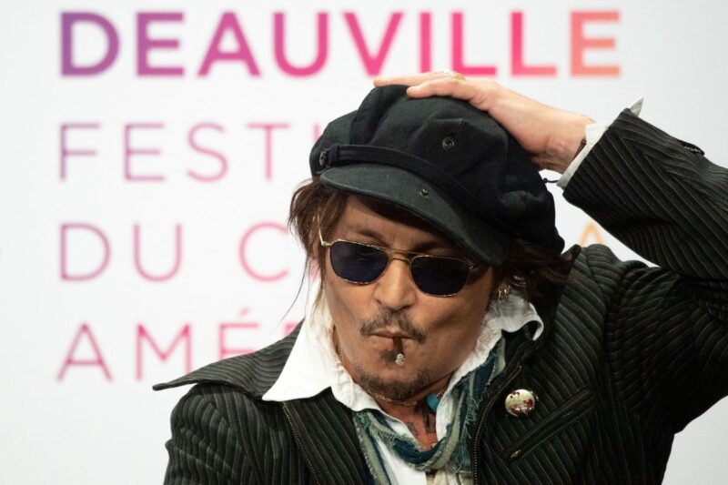 Johnny Depp smoking in a black jacket, glasses, and hat