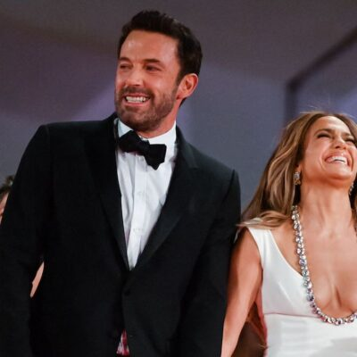 Ben Affleck in a tuxedo laughing with Jennifer Lopez in a white dress