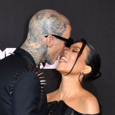 Travis Barker in a black suit kissing Kourtney Kardashian in a black dress