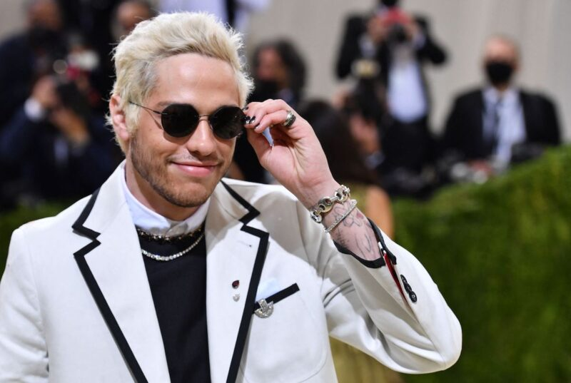 Pete Davidson smiling in black sunglasses and a white suit