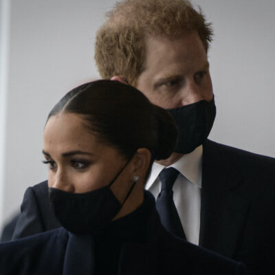 Prince Harry and Meghan Markle in black masks in a line